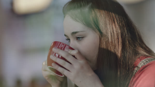 cu. teenage girl sips latte and stares out window in local coffee shop. - getränk stock-videos und b-roll-filmmaterial