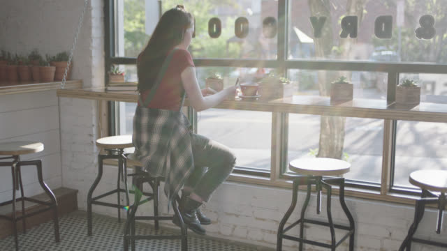 WS. Teenage girl sips latte in sunny window seat of downtown coffee shop.