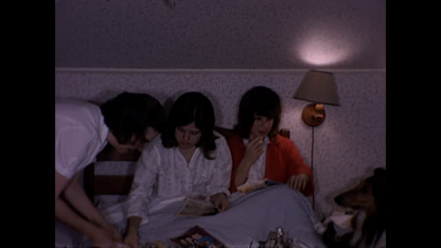 1965 Teenage girl sisters open Christmas presents in bed - Home Movie
