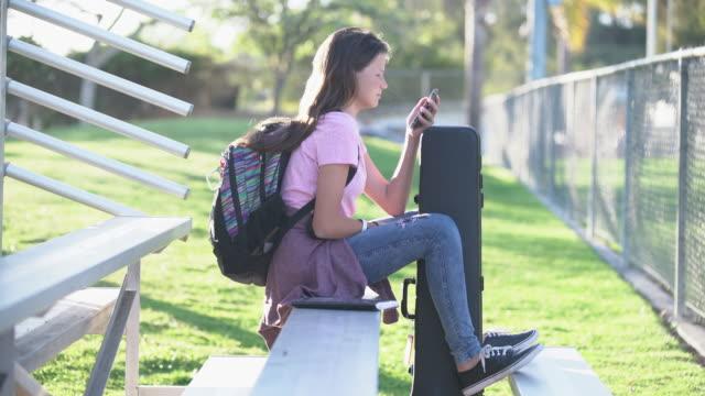 WS Teenage girl sitting in the bleachers at school