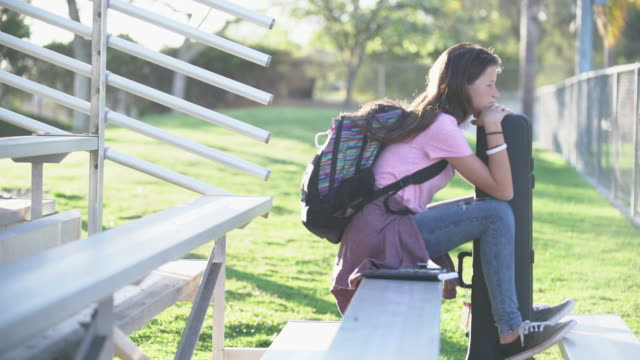 ws teenage girl sitting in the bleachers at school - junior high stock videos & royalty-free footage