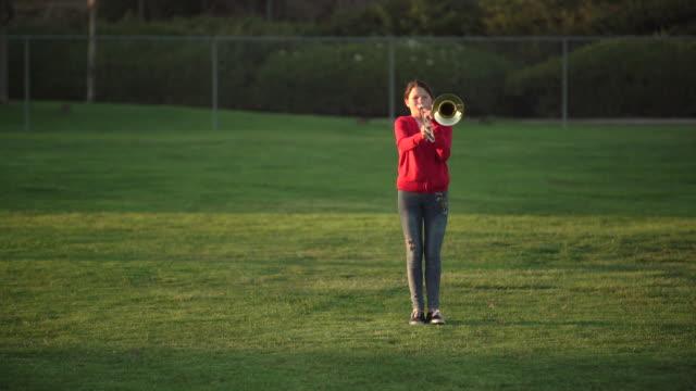 teenage girl sitting in the bleachers at school - trombone stock videos & royalty-free footage