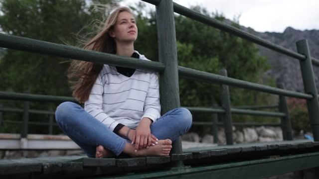 vídeos de stock, filmes e b-roll de adolescente sentada em uma ponte em limone sul garda e desfrutando da vista do lago garda - só uma adolescente menina