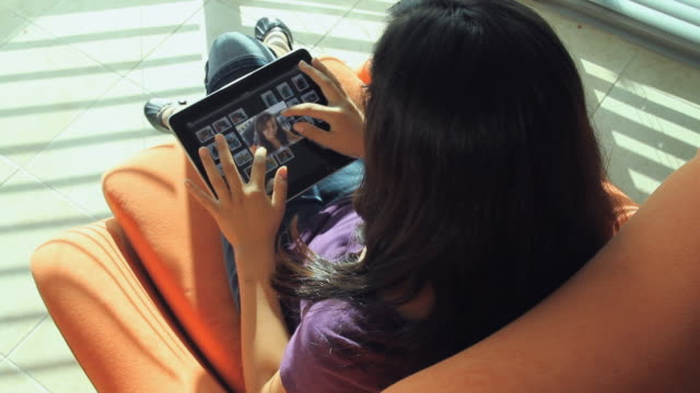 ms ha teenage girl (13-14) sitting on armchair and browsing pictures on digital tablet / miami, florida, usa - one teenage girl only stock videos & royalty-free footage