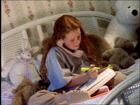 teenage girl sitting on bed talking on phone while highlighting pages in textbook - landline phone stock videos and b-roll footage
