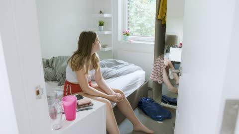 stockvideo's en b-roll-footage met teenage girl sitting on bed - solitair
