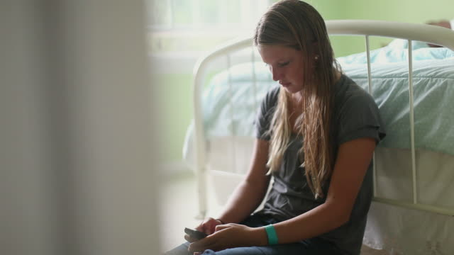 vidéos et rushes de ms selective focus teenage girl (16-17)sitting on floor at foot of bed and using cell phone / cazenovia, new york, usa - text