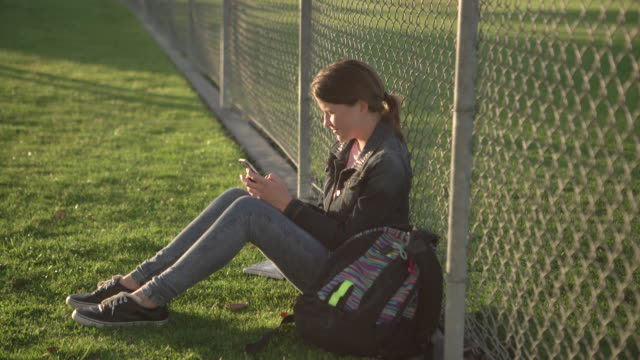 ws teenage girl sitting on the grass leaning against a fence at school - secondary school child stock videos & royalty-free footage