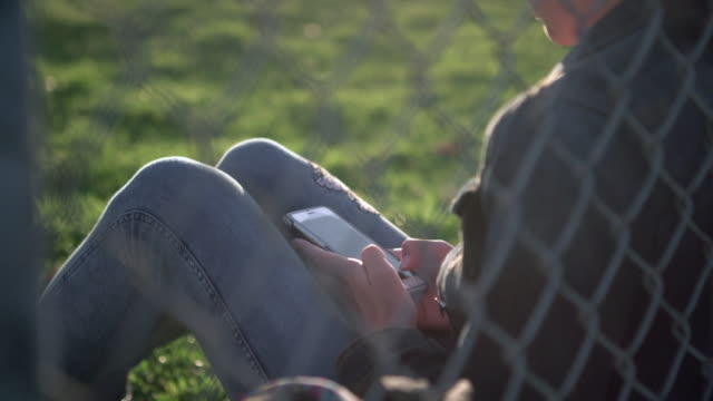 rv ms teenage girl sitting on the grass leaning against a fence - educazione secondaria video stock e b–roll