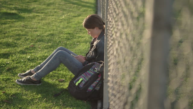 ws teenage girl sitting on the grass leaning against a fence - tribüne stock-videos und b-roll-filmmaterial