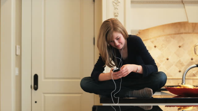teenage girl sitting on the kitchen counter listening to her mp3 player