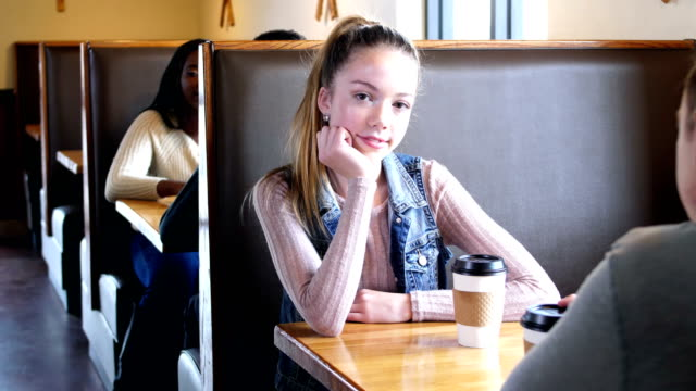 teenage girl sitting with boyfriend in coffee shop - hand on chin stock videos & royalty-free footage