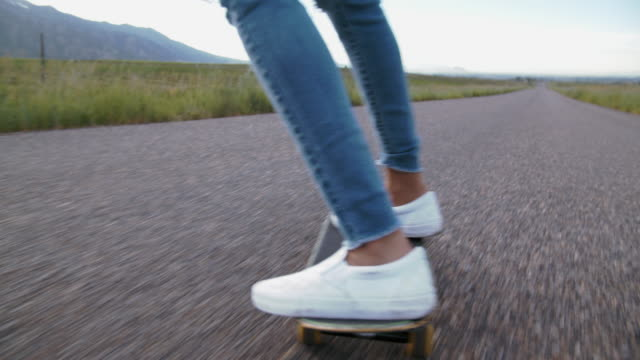 tu teenage girl skateboarding down a road - trousers stock videos & royalty-free footage