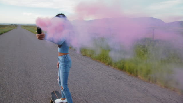 vídeos de stock e filmes b-roll de ws teenage girl skateboarding down a road - cor de rosa