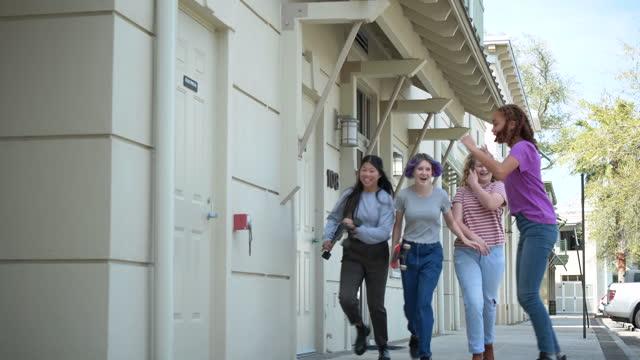 teenage girl skateboards by her friends on sidewalk - 12 13 years stock videos & royalty-free footage