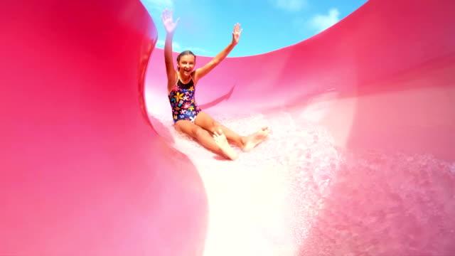 stockvideo's en b-roll-footage met tiener meisje glijden naar beneden gigantische waterglijbaan - attractiepark