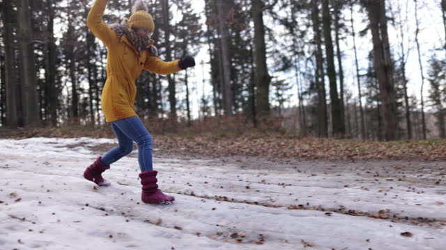 teenage girl sliding on snow in winter forest - dolly shot stock videos & royalty-free footage