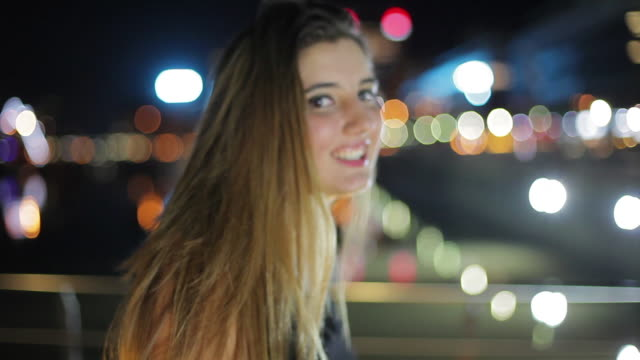 teenage girl smiling and running hands through hair outdoors at night portrait - one teenage girl only stock-videos und b-roll-filmmaterial