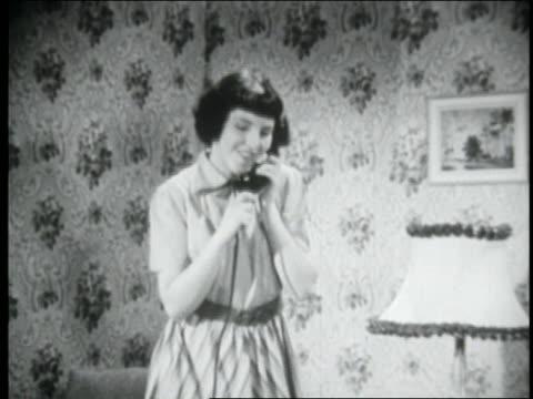 vídeos y material grabado en eventos de stock de b/w 1950 teenage girl smiling + talking on telephone as she sits down - sólo chicas adolescentes