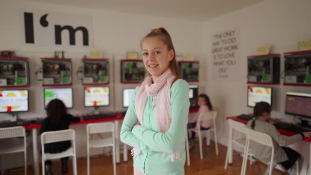 vídeos y material grabado en eventos de stock de adolescente de pie en el aula moderna de la escuela de computación - brazos cruzados