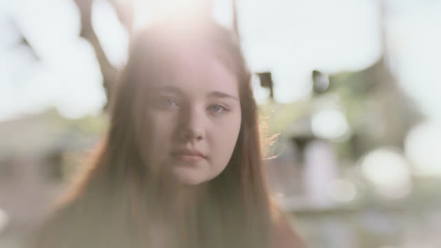 MS SLO MO. Teenage girl stares at camera as sun shines through window of coffee shop.