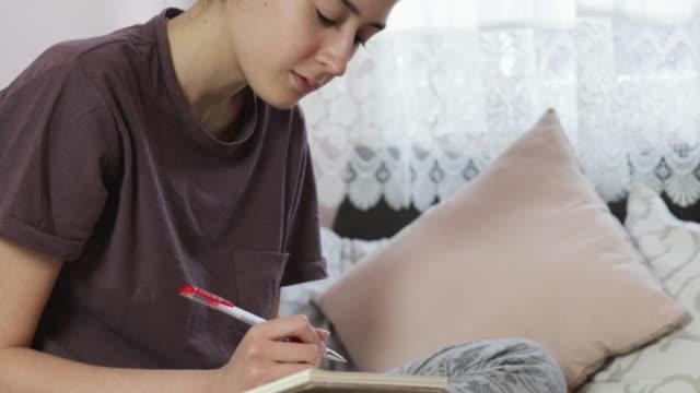 covid-19パンデミックの間に自宅で勉強している10代の少女 - remote location点の映像素材/bロール