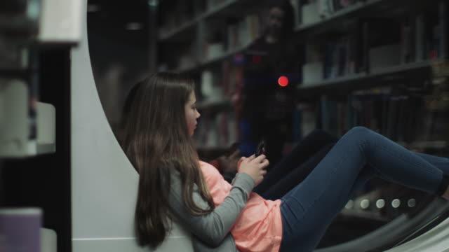 teenage girl studying in library with smart phone, night time - endast en tonårsflicka bildbanksvideor och videomaterial från bakom kulisserna