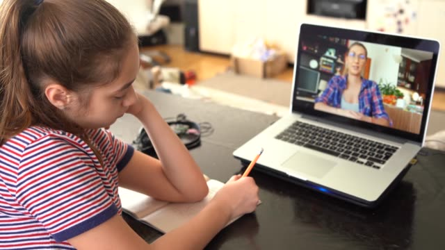 4k teenage girl studying with video online lesson at home   family in isolation - insegnante video stock e b–roll