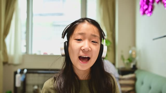 teenage girl studying with video online lesson at home. she is speaking to the camera on a video call. - little girl webcam stock videos & royalty-free footage