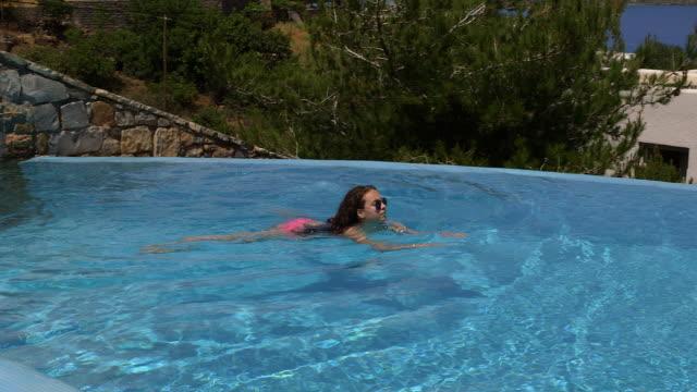teenage girl swimming in infinity pool - utebassäng bildbanksvideor och videomaterial från bakom kulisserna