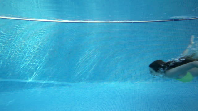 Teenage girl swimming underwater