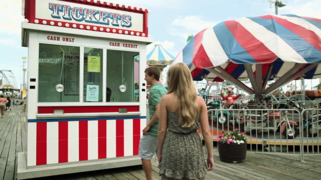 vidéos et rushes de teenage girl taking boyfriend to ticket booth in fun fair - allée couverte de planches