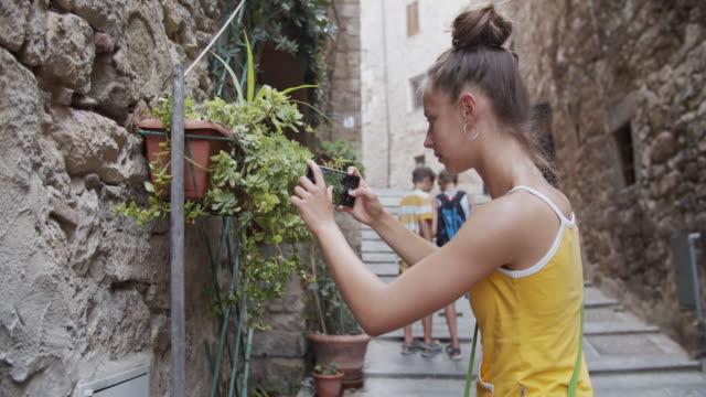 vídeos y material grabado en eventos de stock de chica adolescente tomando fotos en la hermosa ciudad italiana - town