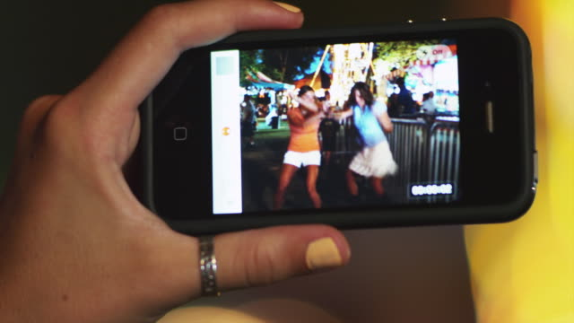cu teenage girl (16-17) taking picture of friends dancing in amusement park / american fork city, utah, usa - flüssigkristallanzeige stock-videos und b-roll-filmmaterial
