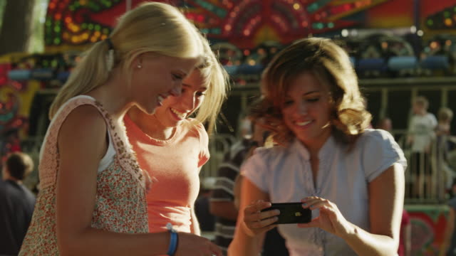 ms pan teenage girl (16-17) taking picture of friends in amusement park / american fork city, utah, usa - weibliche freundschaft stock-videos und b-roll-filmmaterial