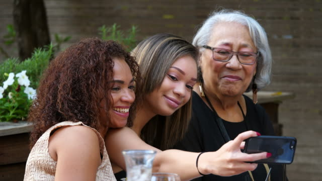 ms teenage girl taking selfie with smartphone of mother and grandmother during outdoor family dinner party - 思い出点の映像素材/bロール