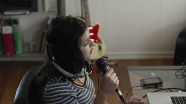 ms ds teenage girl (16-17) talking into microphone and using laptop / orem, utah, usa - orem utah stock videos & royalty-free footage