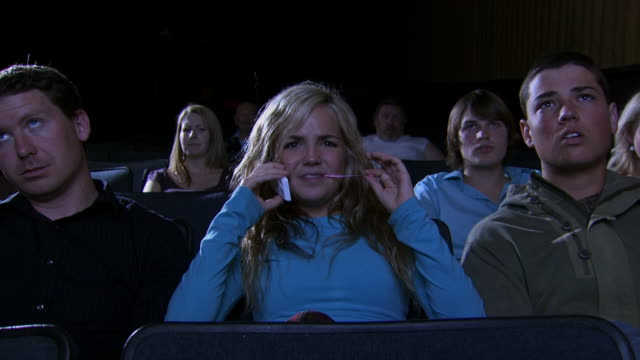 Teenage girl talking on cell phone at movie theater
