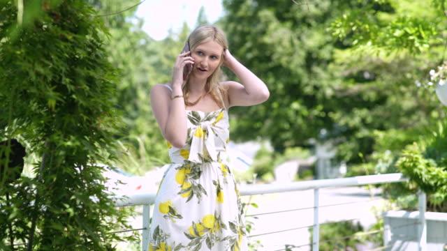 vidéos et rushes de teenage girl talking on the phone outside - robe d'été