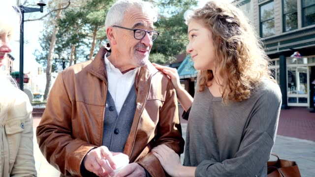 Teenager-Mädchen spricht mit ihrem Großvater im freien sitzend