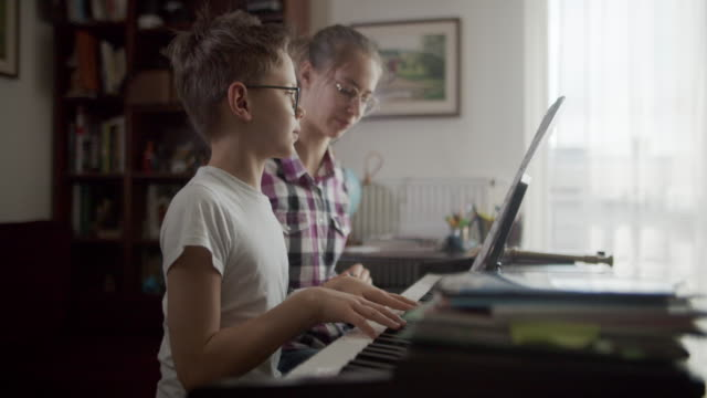 teenage girl teaching her brother to play piano - imgorthand stock videos & royalty-free footage