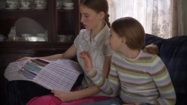 MS PAN Teenage girl (16-17) teaching younger sister (10-11) knitting / Newark, Illinois, USA