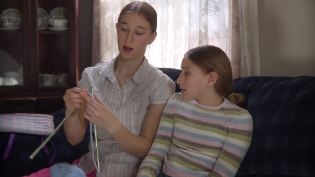 ms teenage girl (16-17) teaching younger sister (10-11) knitting / newark, illinois, usa - stricken stock-videos und b-roll-filmmaterial