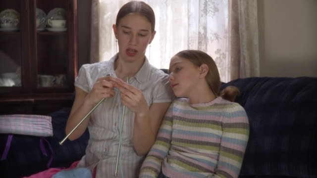 MS TD Teenage girl (16-17) teaching younger sister (10-11) knitting / Newark, Illinois, USA