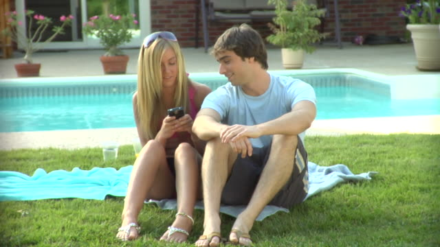 MS, Teenage girl (16-17) text messaging beside swimming pool, teenage boy (16-17) looking at her phone, Middlesex, New Jersey, USA