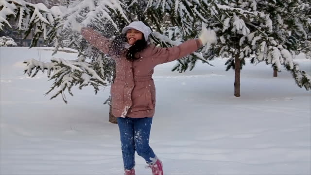 Teenage girl throwing snow in the air in winter holidays