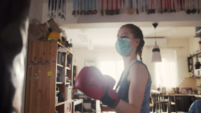 teenage girl training boxing with punching bag - home interior stock videos & royalty-free footage