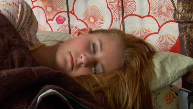 vidéos et rushes de cu, pan, teenage girl (14-15) turning off alarm clock and waking up in bed - seulement des jeunes filles