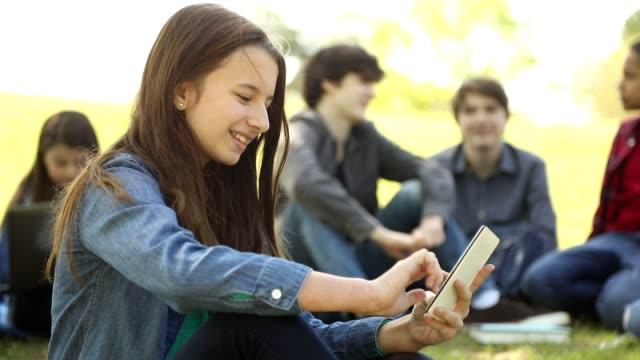 vídeos y material grabado en eventos de stock de una adolescente usando un teléfono celular en el parque o en el campus escolar. - 12 13 años