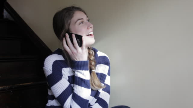 ms teenage girl using cell phone inside on set of stairs / seattle, washington, united states - one teenage girl only stock videos & royalty-free footage